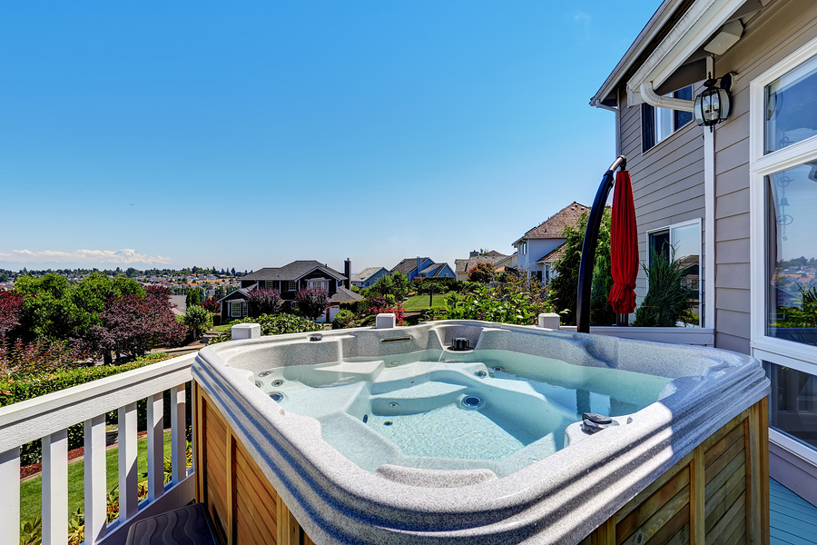 Close-up of wooden hot tub. Luxury house exterior. Blue sky background. Northwest USA